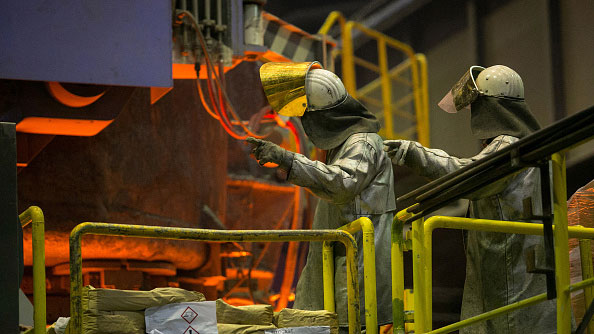 efabd17250c18 Employees gestures as they wear protective clothing beside a continuous  casting machine on the production line