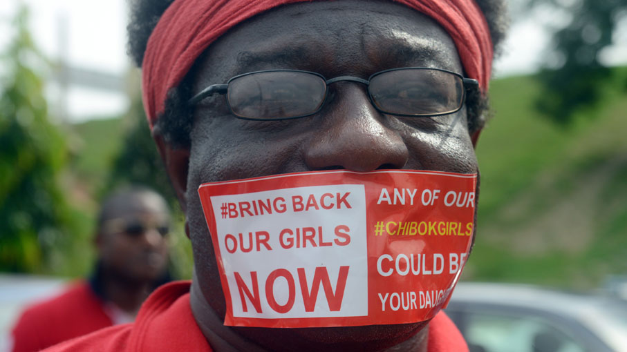56742ceaef0 A man seals mouth with a branded sticker reading  Bring Back Our Girls Now
