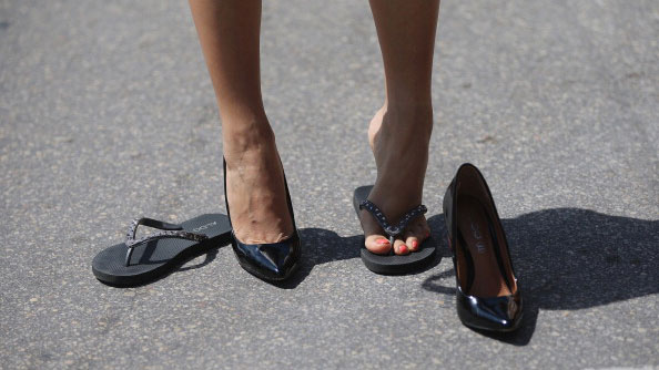 A woman puts on her shoes as she prepares for the Azucar High Heel Race before
