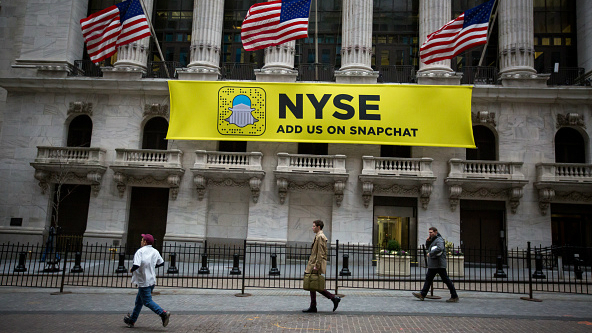 Pedestrians pass in front of a sign that reads  NYSE Add Us On Snapchat  b87c4271ca