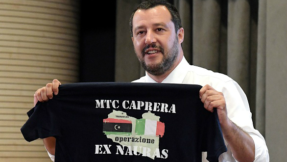 Italy's Interior Minister and Deputy Prime Minister Matteo Salvini shows a t-shirt of the Italian navy with Italian and Libyan flags on a map of Libya at the end of a press conference on June 25, 2018 in Rome.