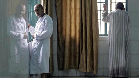 Patients stand near windows inside the al-Rashad mental health facility in Baghdad in March 2006