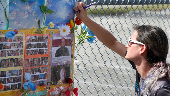 A student writes on a memorial left on a fence surrounding Marjory Stoneman Douglas High School in Parkland, Florida on February 21, 2018.