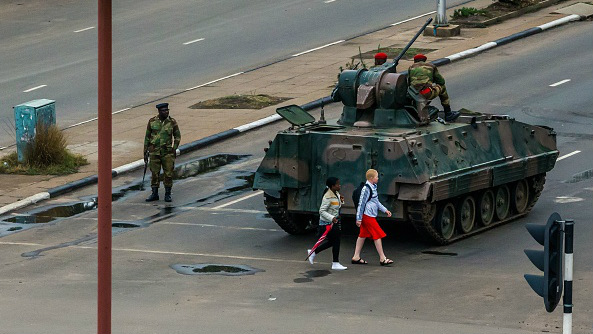 Young women walk past an armoured personnel carrier in the capital Harare on November 15, 2017