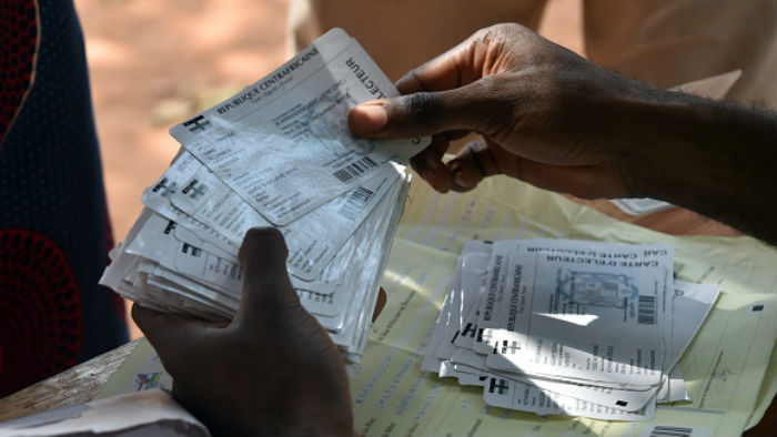 A worker holds voter registration cards during a distribution in Bangui on December 25, 2015 ahead of the presidential elections