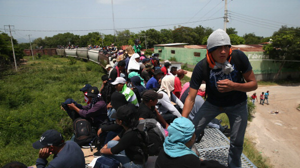 Central American migrants ride on top of a freight train during their journey north through Mexico to reach the United States