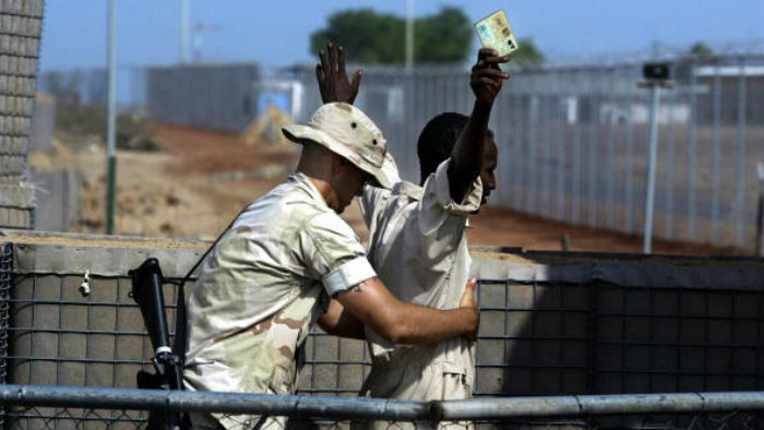 A US marine frisks an employee working at Camp Lemonnier in Djibouti, on September 17, 2003
