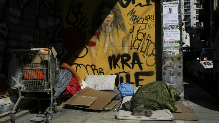 A homeless man sleeps on a pavement in Athens, on February 25, 2015
