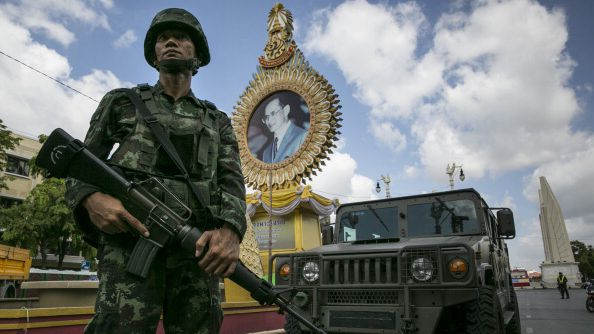 A soldier stands in front of a picture of King Bhumibol in Bangkok on May 23, 2014, as the coup gathers steam
