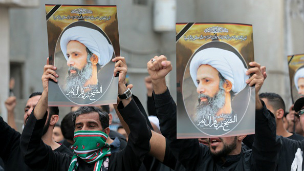Saudi Shia men hold placards showing prominent cleric Nimr al-Nimr during a protest on January 8, 2016, in eastern Saudi Arabia