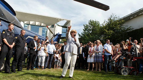 German Chancellor Angela Merkel greets members of the public at the annual Chancellery open-house day on August 28