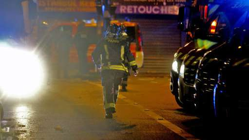 A rescue worker runs after an explosion in the 10th district of Paris on Friday, November 13, 2015