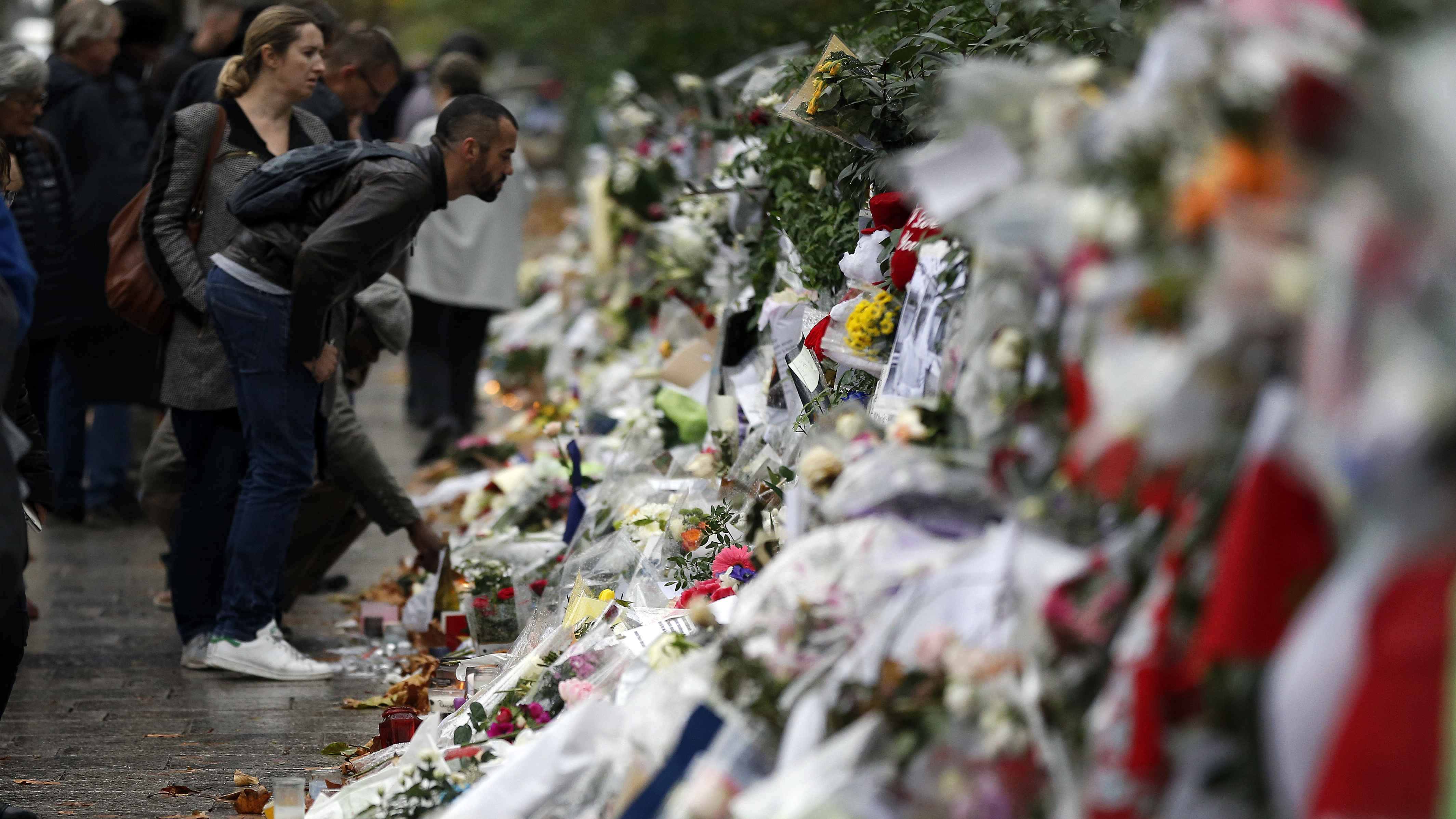 People look at flowers and card tributes placed outside the Bataclan concert hall in Paris, Thursday, Nov. 19, 2015
