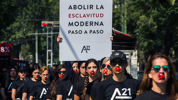 People wearing black shirts and bearing red tape on their mouths walk during the third annual edition of the 'Walk for Freedom' against modern slavery, in Guadalajara, Mexico, on October 15, 2016.