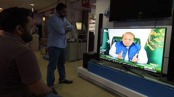 Pakistani people in an shop in Islamabad watch as Prime Minister Sharif announces the formation of a judicial commission