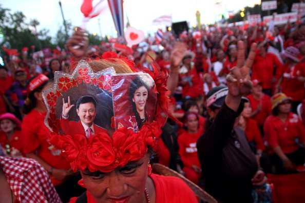 A Shinawatra supporter with pictures of Thaksin and Yingluck on her head at rally in May 2010