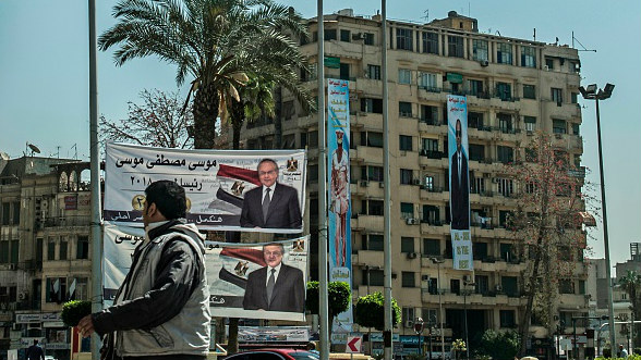A man walks past presidential election campaign banners promoting Egyptian President Abdelfattah al-Sisi (R) and his only opponent, Moussa Mostafa Moussa (L), in Cairo on March 7, 2018.