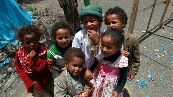 Yemeni children pose at a makeshift camp housing internally displaced persons on April 16, 2016