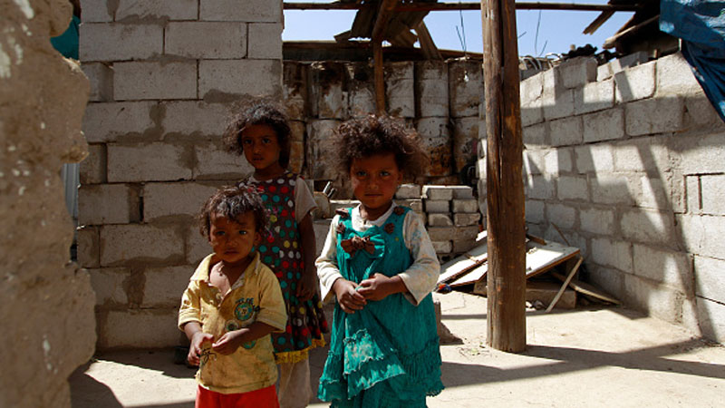 Yemeni children stand inside their house, destroyed several months ago in an air strike in the capital Sanaa